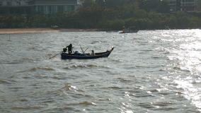 Two Thai fishermen sail on small wooden boat on strong waves to fish. Two Thai fishermen sail on a small wooden boat on strong waves to fish stock video footage