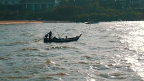 Two Thai fishermen sail on small wooden boat on strong waves to fish. Two Thai fishermen sail on a small wooden boat on strong waves to fish stock footage