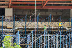 Two Thai laborers at work site. They are on scaffold used for construction of new building stock images