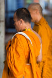Two Thai monks standing and praying in Koh Chang Island. Royalty Free Stock Photo