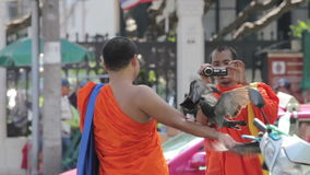 Two Thai monks taking photograph with pigeons on October 12, 2014 in Bangkok, Thailand. stock video