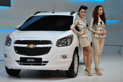 Two Thai presenters next to a Chevrolet Spin Stock Image