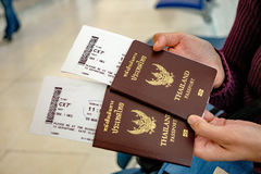Two of Thailand passports in hands with boarding passes.  stock image