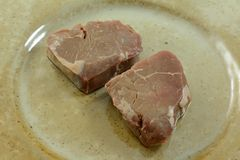 Two thawed frozen raw top sirloin steak fillets. On plate as part of preparation for seasoning or grilling Stock Photos