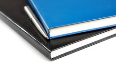 Two thick writing-books with a pen. On  white background Stock Image