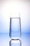 Two-thirds full drinking glass with reflection. On white and blue background royalty free stock image
