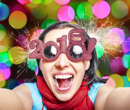 Two thousand and sixteen. Girl in glasses taking selfie. New Years concept Stock Photography