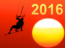 Two thousand sixteen New year. Kite-surfing on orange sunshine background with Number 2016 royalty free stock image