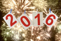 Two thousand sixteen New year. Sheets of a cardboard with numbers 2016 (New year of Two thousand sixteen ) hanging on a clothesline. With holiday fireworks in stock photography