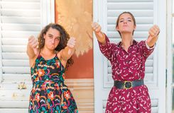 Two thumbs down by young girls. Two young best friend giving two thumbs down and disapproving royalty free stock photo