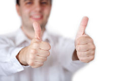 Two thumbs up. Man in white shirt is showing two thumbs up gesture and smiling Royalty Free Stock Image