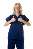 Two thumbs up. Young pretty blond woman healthcare worker wearing blue scrubs and a stethoscope holding two thumbs up on white Stock Image