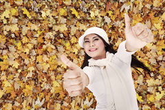 Two thumbs up in Autumn park. Beautiful girl laying on Autumn leaves raising two thumbs up Royalty Free Stock Photography