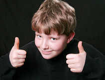 Two thumbs up boy. Young kid giving happy two thumbs up expression of approval Royalty Free Stock Image