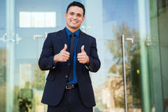 Two thumbs up. Good-looking Latin young man wearing a suit and giving both thumbs up while smiling excitedly Royalty Free Stock Photo