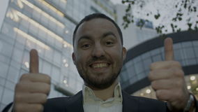Two thumbs up, portrait of young business man on. Portrait of young business man on office building background. Caucasian man with beard smiling stock video