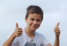 Two thumbs up from young boy. A young boy shows two thumbs up Stock Image