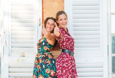 Two thumbs up by young girls. Two young best friend giving two thumbs up and approving royalty free stock image