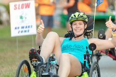 Two thumbs way up for this smiling woman on her recumbent bike. royalty free stock images
