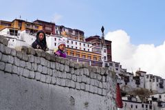The two tibetan girls staying and looking from the wall royalty free stock photography
