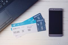 Two tickets are on the table with a phone and laptop. Concept of buying the online ticket booking for travel. Two tickets are on the table with a phone and Stock Images