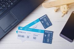 Two tickets are on the table with a phone and laptop. Concept of buying the online ticket booking for travel. Two tickets are on the table with a phone and Stock Photos