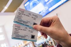 Two tickets in a woman`s hand for travel by high-speed train CRH. Two tickets for a modern high-speed train CRH in the hands of a woman at the train station royalty free stock image