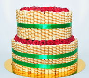 Two tier cake decorated with finetti sticks and fresh raspberry stock images