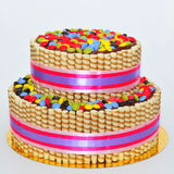 Two tier chocolate decorated with finetti sticks and colorful candy stock photo