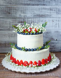 Two-tier cream cheese wedding cake with blueberries and strawber Royalty Free Stock Image