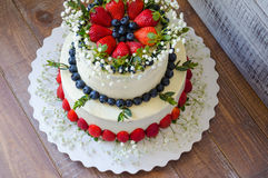 Two-tier cream cheese wedding cake with blueberries and strawber Stock Images