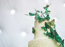 Two-tier wedding cake is decorated with green butterflies Royalty Free Stock Photo
