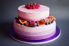 Two tiered purple cake with fruit on dark gray background Stock Photography
