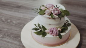 A two-tiered wedding cake, decorated with twigs of greenery and fresh flowers with roses and peonies, stands on a wooden. A two-tiered wedding cake, decorated stock video