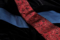 Two ties on black velvet crossing on top of the other Stock Image