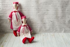 Two tilde dolls in red dresses, and white aprons, and in red kalpaks sit on a light background. Interior dolls. There is a place. For text. The concept of stock photos