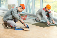 Two tilers at industrial floor tiling renovation. Two industrial tiler builder worker installing floor tile at repair renovation work Stock Photos
