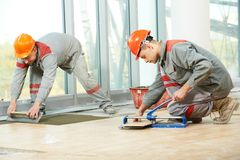 Two tilers at industrial floor tiling renovation Royalty Free Stock Photography