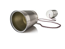 Two Tin Cans Connected by String Isolated on White. Photograph of two tin cans connected by string and isolated on white, representing communication technology Stock Image
