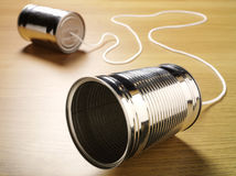 Two tin cans joined with a cord on a wooden background. For primitive communication Stock Photo