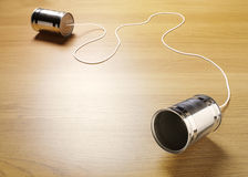 Two Tin Cans Joined with a Cord. On a wooden background for primitive communication. Copy space Stock Photos