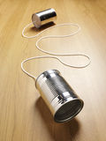 Two tin cans joined with a cord on a wooden background Stock Photo