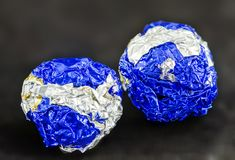 Two tinfoil balls. Two balls colored blue and silver made from crumpled tinfoil royalty free stock photography