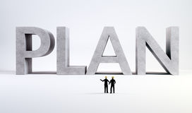 Two tiny engineers overseeing a plan Royalty Free Stock Photo