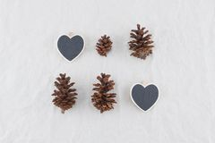 Two tiny heart shape blackboards with pinecones. On muslin fabric background Stock Images