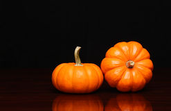 Two tiny pumpkins over black. Halloween Stock Photos