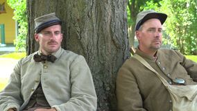 Two tired Civil War soldiers rest by tree stock video