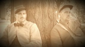 Two tired Civil War soldiers resting by tree (Archive Footage Version). View of Two tired Civil War soldiers resting by tree (Archive Footage Version stock footage