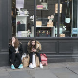 Two tired gitls in jackets with shopping bags sit on the pavement near the store, waiting for friends. Royalty Free Stock Image
