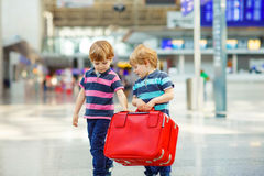 Two tired little sibling boys at the airport Stock Photos